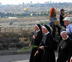 www.ffhl.org #ffhl #holyland Nuns carry palm branches during the annual Palm Sunday procession on the Mount of Olives overlooking the Old City of Jerusalem April 13. Christian pilgrims walked the path that Jesus took when he rode a donkey into Jerusalem.