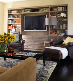 """Let's face it. Gigantic tv's are here to stay.  We recently traded up to a larger tv and placed it in our unused living.  The space is much larger than the """"family room"""" and provides way more seating for our family.  I call the tv my husband's new wife!  I love how this tv looks with the surround shelves and drawers.  Practical."""