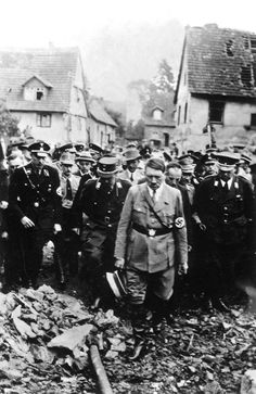 """Adolf Hitler visits the city of Eshelbronn after an allied bombing raid in 1944. This is a rare image of the Führer reaching out to see with his own eyes the suffering of the German people. As a matter of routine, Hitler did not take to the streets of bombed cities -- not even Berlin's."""