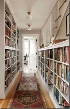 hallway bookshelves, oriental rug, white and bright space