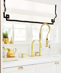 Black and white roman shade with trim details and kitchen sink with brass fittings
