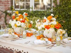 So fresh - oranges or clementines dusting the edges of vases overflowing with poppies and white ranunculus. Love the table apron design!