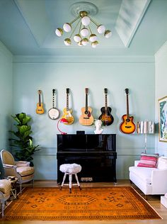 An aqua living room with guitars displayed above a piano.