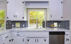 white marble counters in a white kitchen and black hardware