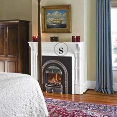 In this master bedroom a closed-off fireplace was opened up to become a focal point. The insert burns gas instead of coal and is made of cast iron, painted and polished to look like pewter.