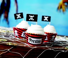 Our Skull and Swords Personalized Cupcake Wrappers features a red and black striped background with your wording imprinted on it for your #PirateParty