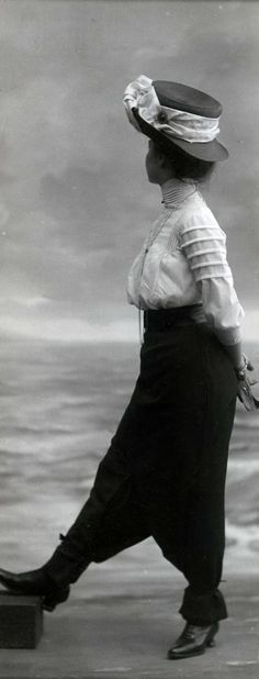 Women's Fashion. Model shows a divided skirt with high waist and a muslin blouse with high neck and a hat. No place, 1911.