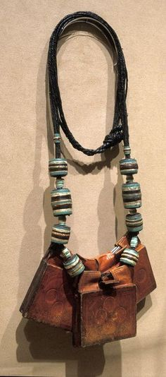 Amulets, or personal protective objects, are worn by Tuareg men and women as protection against natural and supernatural forces. They may contain pieces of paper with verses from the Koran, the Islamic Holy book. Tuareg women tan, dye and sew all leather items while men make metal objects. This necklace probably belonged to a blacksmith, who believed that it would protect his family and livestock from harm.    Over a tenth of Africa's population is nomadic or semi-nomadic.