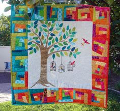 lemon tree tales #quilt with wonky rainbow log cabin border and a tree applique with birdcages in the center