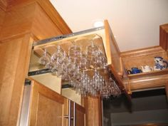 Stemware storage in wasted space above refrigerator