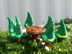 Perfect for a mid summers night dinner party this 7 piece set consists of a table and six chairs. The set is made entirely of polymer clay and made to resemble leafs with a base of a cut log and the table bottom at stump of an old tree, complete with roots.
