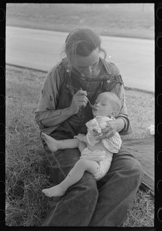 Baby in diaper being fed by migrant worker mother in Oklahoma.  1939