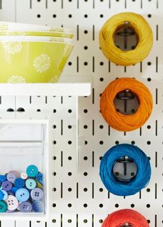 Keep supplies out of the way by employing vertical storage. Pegboards on a wall easily hold anything that can hang, such as these thread balls. Scissors and ribbon also hang perfectly from pegs.