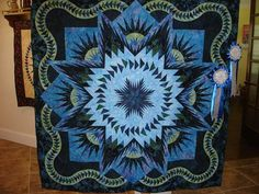 """Glacier Star designed by Quiltworx.com, made by Cherrie Kridler.  My Glacier Star quilt won two first place awards in the 2014 Lakeview Quilt Guild Show: (1) First Place Small Quilt Category (less than 72"""" x 72"""") and (2) First Place Merit Machine Quilting, completed by my friend Denise Green. This quilt show was held in Alvin, TX in May, 2014. A total of 225 quilts were entered in the show so I am very honored with my ribbons."""