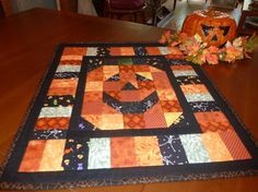 JackOLantern Wall Hanging or Table Topper by Fortheloveofpumpkins, Looks like HST to form the face.