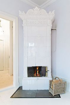 "These types of fireplaces, called ""kakelugn"" in Swedish, are very common in old Swedish apartments, but they are usually quite understated with white tile and small metal doors that open so you can see the fire."