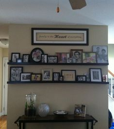 Gallery wall using Ana White's DIY 10 dollar picture ledge plans. Shelves are 6 foot in length. Still need to replace frame models with my own family.