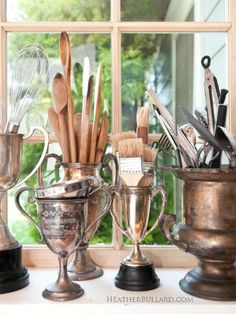 A group of vintage trophies repurposed to hold kitchen tools is brilliantly stylish.