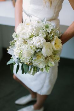 white bouquet of mixed flowers, photo by CarolineRo http://ruffledblog.com/charity-inspired-wedding-ideas #bouquet #weddingbouquet #wedding
