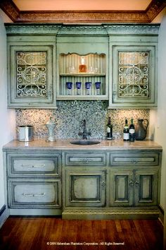 A wet bar done with green cabinets, with a distressed finish. <3