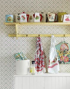 A sweet garden-trellis-print wallpaper, along with vintage soap dispensers and aprons, pretties up the laundry room.