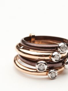 Four stack rings of 18kt rose gold and chocolate gold are hinged together to created this ring.  Five white diamonds are scattered onto the display of the ring and bezel set in 18kt white gold.  Size 7.0.