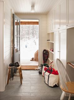 source: Whitten Architects  Farmhouse mudroom features white paneling on walls and ceiling as well as entire wall of built-in cabinets with cubbies next to built-in desk over gray tiled floor in brick pattern. Mudroom with gray door accented with glass panels and wood bench.
