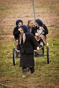 Lancaster Amish girls play on a carriage