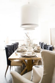 Eclectic dining room design with rustic wood dining table, black leather tufted wingback dining chairs with beige leather cushions with nailhead trim, linen wingback slip-covered captain chairs and white drum pendants with gray ribbon trim.