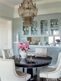 urquoise blue dining room design with gray blue cabinets, round black pedestal dining table with white trim, cream tufted chairs with nailhead trim and gorgeous mesh chandelier.