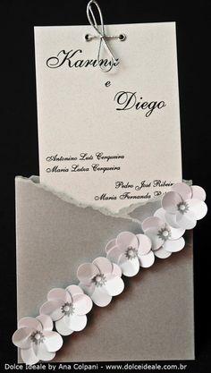 Tema Prata com Flores Brancas Ficha Técnica: Materiais utilizados: papel Marrakech na cor Trigo 180g/m² (interno), papel Relux na cor Aluminium 180g/m², papel Relux na cor Pérola Branca 180g/m² (externo); Formato: 9,5cm (Largura) X 18cm (Altura); Acabamento do convite: flores confeccionadas através da técnica de furadores com efeitos tridimensionais (3D), fitas prateadas e ilhoses.