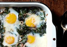 "Company eggs from @Bon Appetit Magazine's ""22 Brunch Recipes for a Lovely, Lazy Morning"" - yields 6 servings; 16g protein, 310 calories. Ingredients: 2 tbsp EVOO, 1 small onion - thinly sliced, 4 garlic cloves - finely chopped, salt & pepper, 2 bunches Swiss chard - thick center ribs+stems removed and leaves coarsely chopped (about 12 c), 1/2 c heavy cream, 12 lrg eggs, and 2 oz (about 1/2 c) sharp white cheddar - grated."