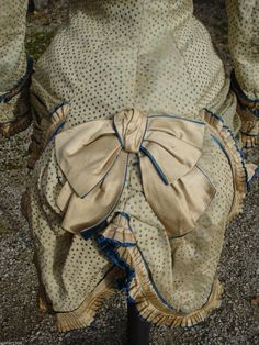 1870s extant French bodice off ebay. Look how low the bow is on the Basque bodice, right at the lower end. More beautiful tiny pleats and piping w/ a contrasting blue color. And the peplum looks like two large petals.