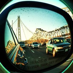In with the new and out with the old.  The new and old Bay Bridges from a side view mirror.