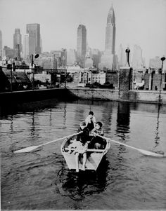 Four young members of the Madison Square Boy's Club rowing a boat in a rooftop pool, Manhattan skyscrapers in the background, Feb. 1950. (Courtesy of the National Archives)