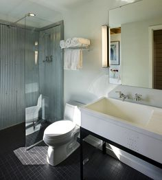 Corrugated Shower with black tile floor. I like the molding around the metal. Could be good for baseboard if I use on all walls.