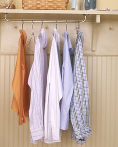 Mount a cheap towel rack to underside of shelving unit to make a hanging rod for clothes in laundry room