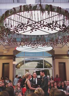 wedding ceremony with flowers hanging from ceiling