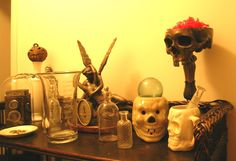 A shelf - box camera, 1880's clock, apothecary glassware, skull mugs, and skull candy dish. Headless Hearseman collection.