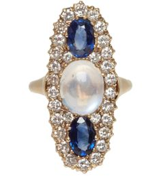 central oval cabochon cut moonstone flanked by oval faceted blue sapphires on each side, surrounded by round brilliant cut white diamonds from Kojis