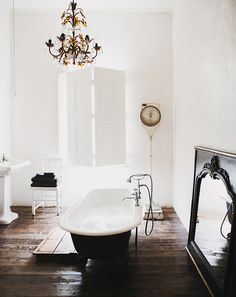 Old world bathroom with hardwood floors, black claw foot tub, antique scale, and chandelier.
