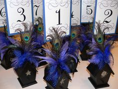 Could be used as centerpieces as well...Birdhouse table number holders with Peacock, maribou and guinea feathers in your choice of colors. $7.25, via Etsy.