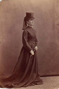 This cabinet card dates to the first half of the 1880's. The habit looks very much like 1880's day dress (minus the bustle), with the button up bodice and the severe look of 1880's costume. The top hat would have been made out of silk and has a spotted veil tied around the crown to feminize the look. The bodice is cut like a day bodice, but probably with slightly less boning in it and looser sleeves to allow movement when riding. Sidesaddle aprons (this is what a sidesaddle skirts are called), had always been cut very full allowing the wearer to look very elegant on horseback. They got narrower the 1890's giving us today the modern apron.  (L. Hidic)