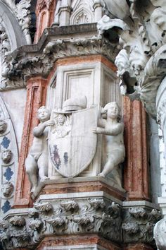 Porta della Carta Putti Sculptures -- Doges' Palace, Venice, Italy    These putti carved to the right of the statue of the doge hold his coat of arms, with his Doge's cap on top. The rosy marble framing this arrangement is lovely. Imagine the polychrome on the Doge's coat of arms. The Venetians were brave in battle, and in their use of color.