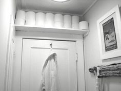 Narrow shelf above the door to store the toilet paper in a small bathroom