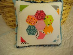 english paper pieced flower on a quilted pillow