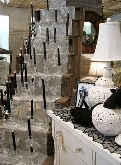Black candles in clear glass/crystal holders against lace. Look like they're floating