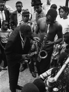 Sidney Poitier is captured giving an impromptu jazz concert along side with Sonny Stitt on the street corner. Photo by Lacey Crawford, circa 1960s.