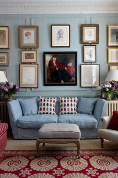 Annabel Astor's drawing room walls are painted in Farrow & Ball's 'Light Blue', on top of which hangs a large collection of pictures and family portraits