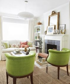 A great mix of old & new in this white & green living room with white sofa, Noguchi light and matching green armchairs